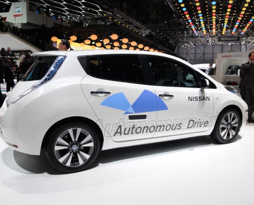 A white car, with automatic drive printed on it. Driverless car.
