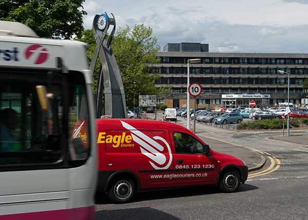 Eagle Couriers van on road beside a bus